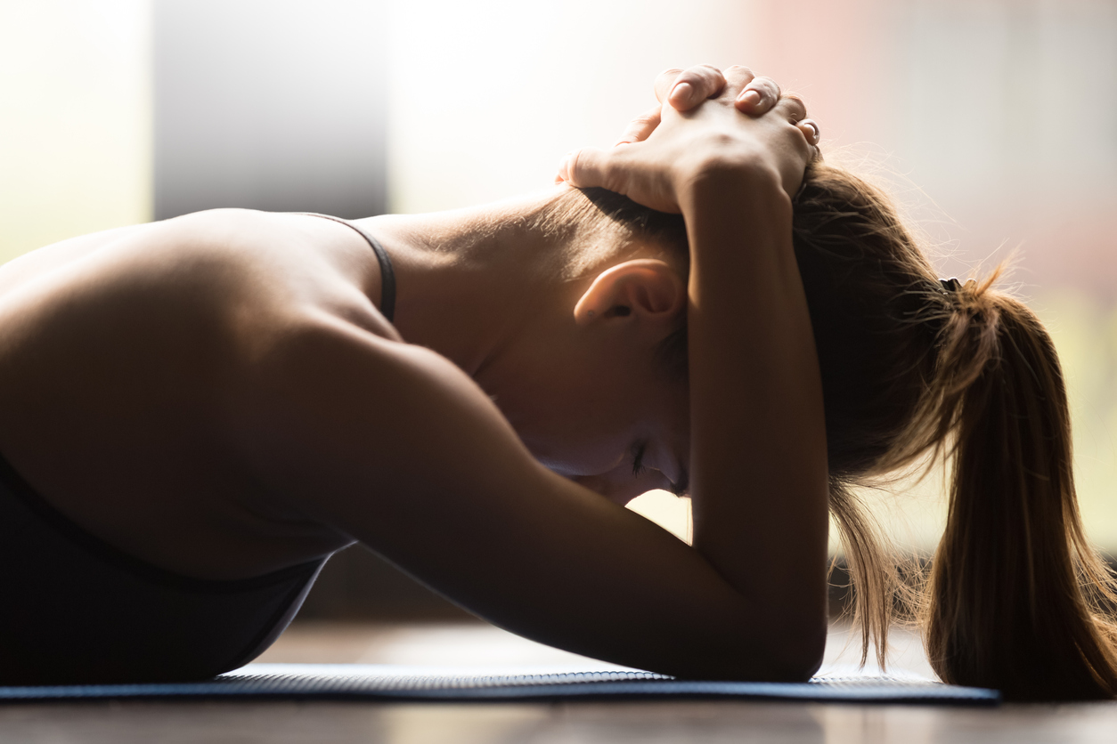Young woman practicing yoga, supporting neck muscle groups, pose to muscle group against neck injuries, working out, wearing sportswear, indoor close up view, yoga studio